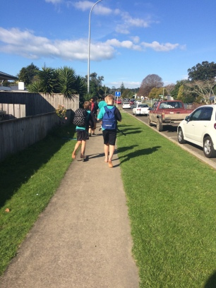kids walking and even scootering home from school, shoeless
